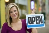2377964-pretty-blond-smiling-woman-holding-up-an-open-sign-with-urban-background